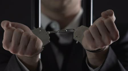 kajdanki : Arrested businessman in prison cell showing handcuffs closeup, financial fraud Wideo