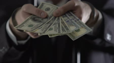 from behind : Handcuffed oligarch standing behind prison bars and holding money, bribe offer Stock Footage