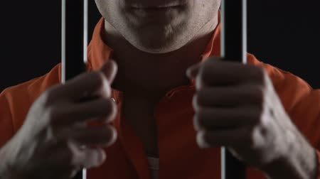 maniac : Cruel serial killer holding jail cell bars, prisoner hands closeup, law breaking