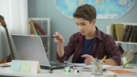 öğrenme : Boy successfully coping with homework, distance education for schoolchildren Stok Video