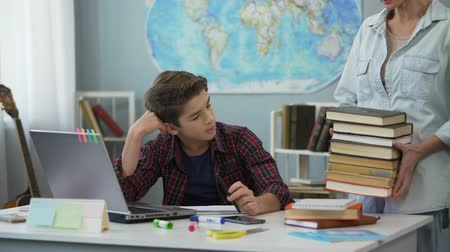 compromise : Teenager shocked by number of books for summer reading brought by strict mother Stock Footage