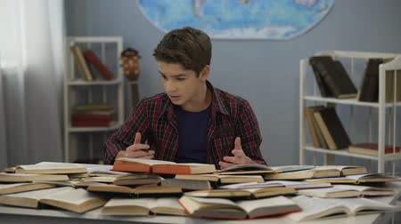 schoolbook : Schoolboy absently looking at huge pile of open books on table, doing homework