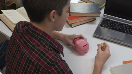 alfabetização : Boy making wish and throwing coin into piggy bank, saving money for dream Stock Footage