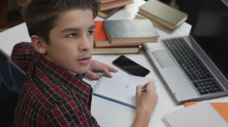 popa : Child reluctantly doing homework under close attention of strict parents