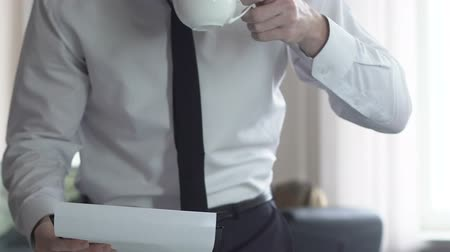 dosya : Lawyer reading client case file at office, businessman drinking cup of coffee Stok Video