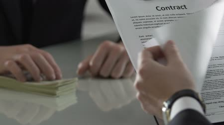 venality : Corporate manager signing paper agreement with cash on table, investment deal