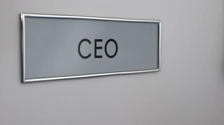 szervez : Chief executive officer door, hand knocking closeup, company management, boss