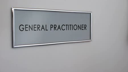 knock : General practitioner office door, hand knocking closeup, preventive medical care