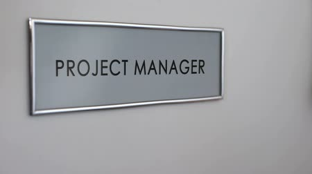 brifing : Project manager office door, hand knocking closeup, developing business strategy