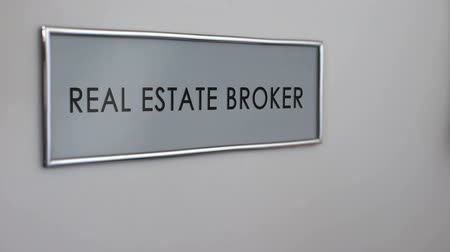 knock : Real estate broker office door, hand knocking closeup, apartment purchase deal