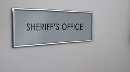 helyettes : Sheriff office door, hand knocking, law enforcement officer, crime prevention