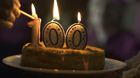 üdvözlet : Hand lighting candles 100 on cake, company anniversary celebration, ceremony