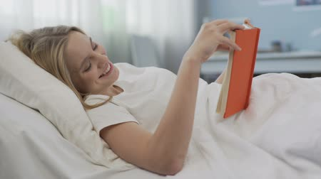 verse : Smiling delighted teenage girl reading novel about romantic love, lying in bed