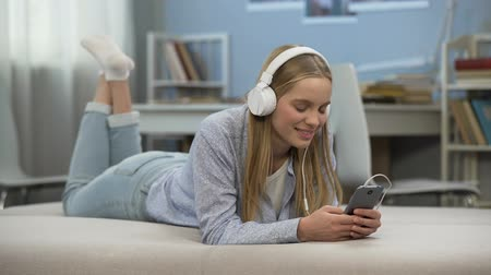 megjegyzés : Delighted teenage girl wearing headphones, listening to music, relaxation time Stock mozgókép