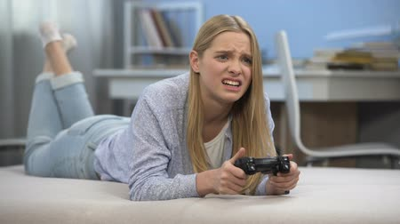 perdedor : Emotional teen girl playing video game at leisure time, upset by virtual failure
