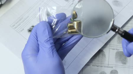 evidência : Investigator analyzing bullets evidence from murder scene using magnifying glass
