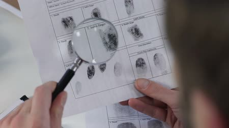 evidência : Police officer checking fingerprints file with magnifying glass, identification