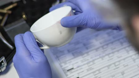 forensic : Criminal specialist taking lipstick print from white cup from murder scene Stock Footage