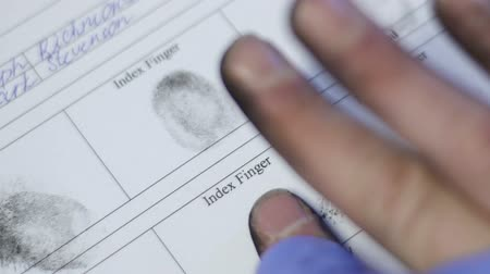 criminology : Police officer taking fingerprints of prime suspect, biometric identifier mark