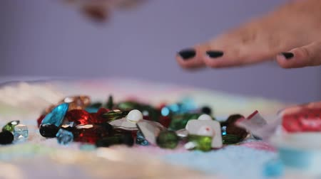pingente : Female hand laying out colorful crystal beads on table for jewelry design.