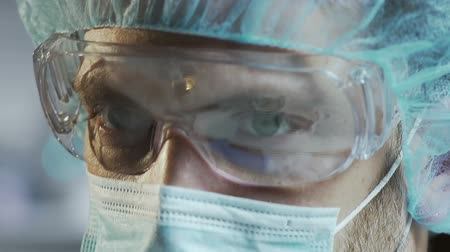 помощник : Medical scientist in protective glasses working in laboratory, face close up Стоковые видеозаписи