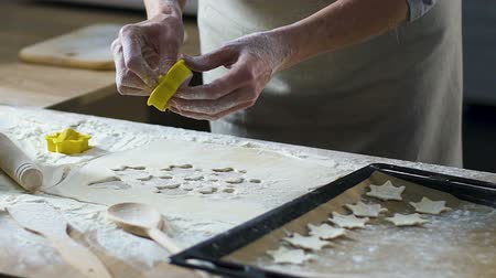 baker : Female hands cutting out shapes from rolled dough with star and heart cutters Stock Footage