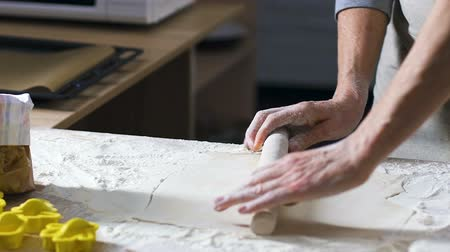 pin up : Female hands roll out dough with rolling-pin on wooden table covered in flour Stock Footage