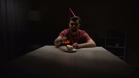 despedida de solteros : Lonely man lighting candle on birthday cupcake, sitting alone in dark room