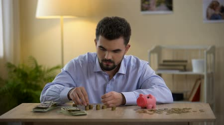 alfabetização : Man counting money and putting coin in piggy bank, financial literacy, budget Vídeos