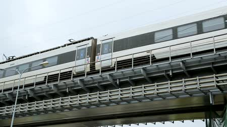 бросаясь : Modern train rushing along railway bridge, public transportation, urban metro