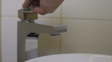 csőhálózat : Plumber checking work of water tap after installing new equipment in bathroom