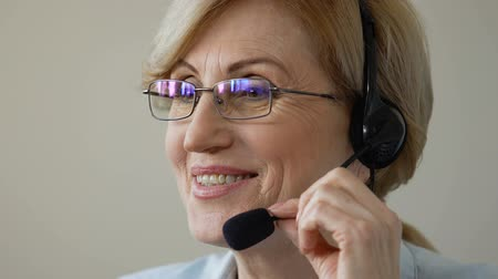 телефон доверия : Friendly smiling old woman in headset speaking with client, call center support