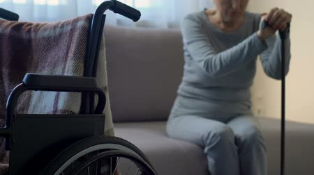 rehabilitasyon : Sad senior lady looking at wheelchair, feeling lonely and abandoned, depression