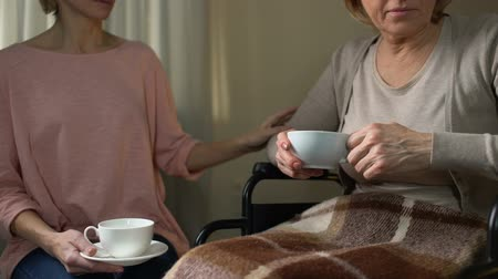 senior lifestyle : Daughter trying to persuade mom to go to nursing home, sitting over cup of tea