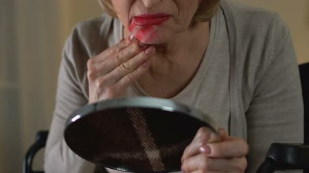 důchodce : Old woman in wheelchair smearing lipstick over her face and hysterically crying
