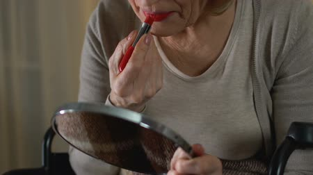 remembering : Woman in her 70 putting on red lipstick to forget about her age and disabilities