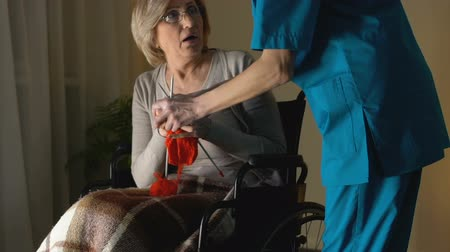 трепет : Nurse taking away needles from woman with Parkinsons disease trying to knit Стоковые видеозаписи