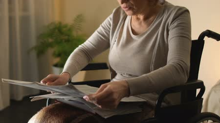 rehabilitasyon : Intelligent woman in wheelchair reading newspaper, old age leisure. Stok Video