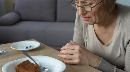 isteyen : Senior lady feeling heaviness and stomach pain after eating pie, pills on table