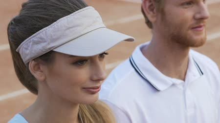 shy : Attractive female athlete looks at tennis player beside, both smiling, flirting