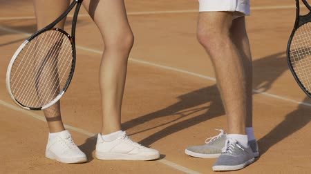teniszütő : Tennis players talking on court, sports shoes for athletes, feet close-up