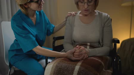 precisão : Nurse talking heartily to old woman in wheelchair supporting her, elderly home Stock Footage