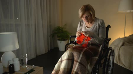 вязание : Old tired woman in wheelchair wearing glasses trying to knit, poor eyesight