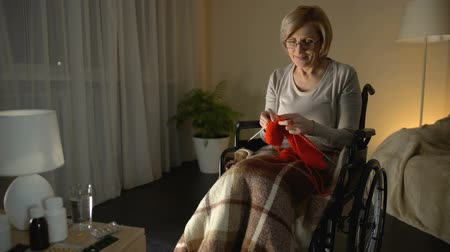 cosiness : Cheerful old woman sitting in wheelchair knitting scarf, taking care of children Stock Footage