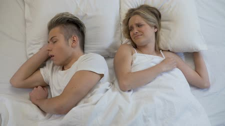 хмурый : Annoyed woman closing ears while man snoring loudly in bed, apnea disease Стоковые видеозаписи