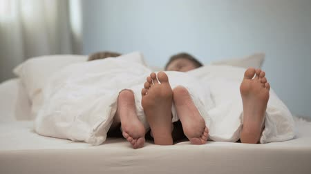 compreensão : Happy couple feet in honeymoon bed, lovely conversation in morning, marriage