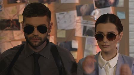 evidência : Professional detectives of private investigation service putting on sunglasses
