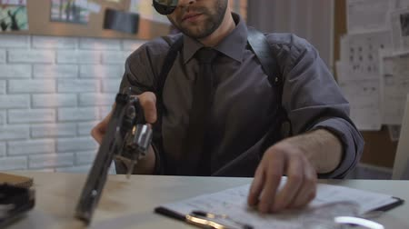 investigador : Confident detective charging gun sitting in police station, protection and order