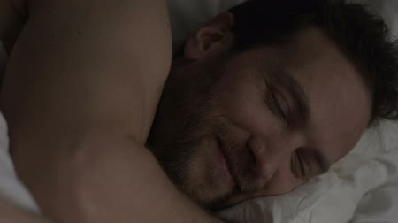 восхищенный : Adult man lying in bed, smiling before falling asleep.