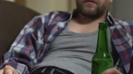 meteliksiz : Drunk bearded man sitting on couch and drinking beer. Stok Video